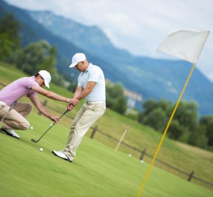 Golf pro teaching male golfer on putting green.