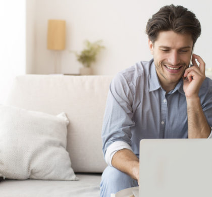 Always In Touch. Businessman Talking On Phone Working On Laptop At Home. Free Space