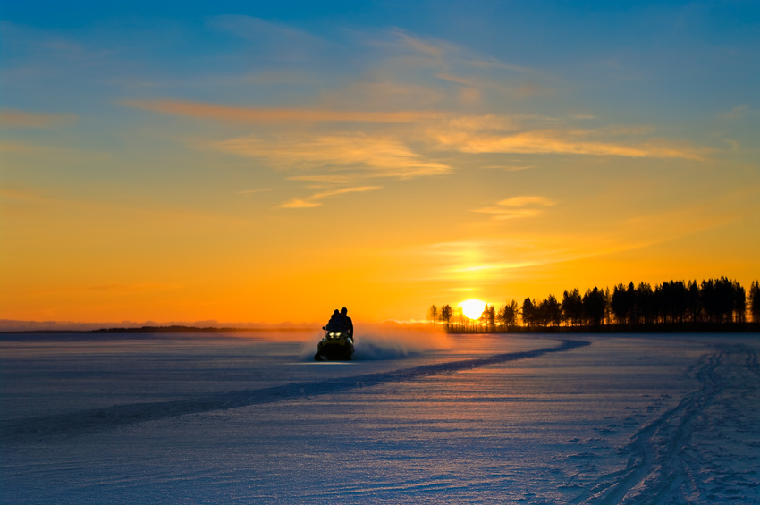 Blue and orange sunset on winter snowy lake and snowmobile with people on it.